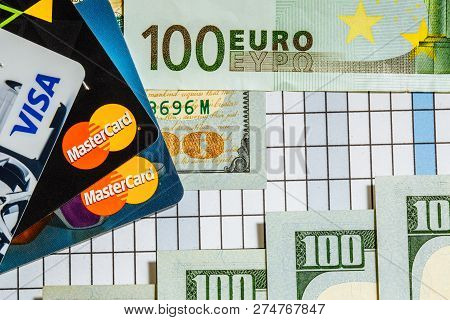 Bank Cards. A Hundred Euro Banknote. And A Hundred Dollar Bills On The Background. Worlds Major Curr