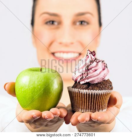 Smiling Woman Gives A Choice, Deciding Apple Or Cupcake, Healthy Or Unhealthy Food.