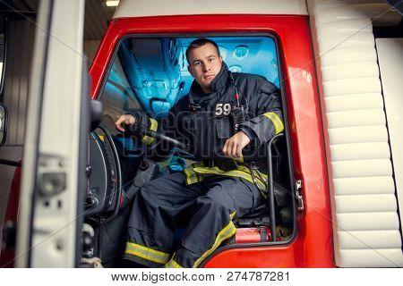 Photo of fireman man sitting in fire truck