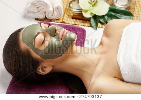Spa Clay Mask. Woman With Clay Facial Mask And Cucumbers On Eyes In Beauty Spa. Skincare. Beauty Con