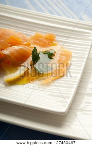 smoked salmon marinated on olive oil on dish