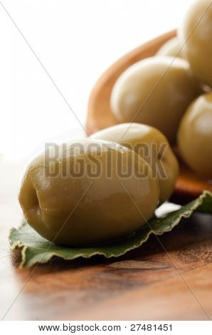 green olives over the spoon close up