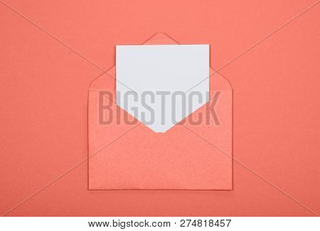 Top View Of White Blank Card In Coral Color Opened Craft Envelope On Coral Background. Minimal Conce
