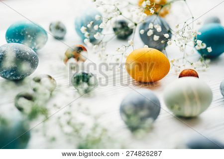 Stylish Easter Eggs With Spring Flowers On White Wooden Background. Modern Easter Eggs Painted With