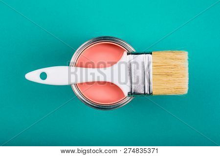 Brush With White Handle On Open Can Of Living Coral Paint On Blue Pastel Background. Color Of The Ye