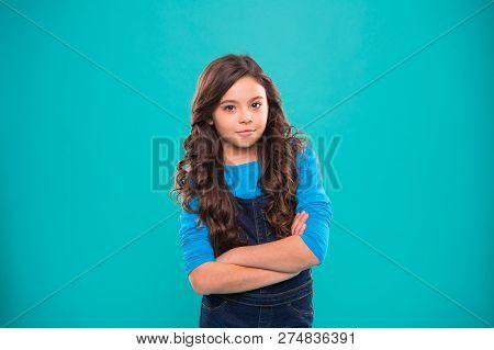 Upbringing Confidence. Kid Girl Long Hair Posing Confidently. Girl Curly Hairstyle Feels Confident.