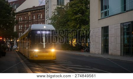 Public transportation concept. Yellow electric tram travels at night at Berlin, Germany. City and people background.