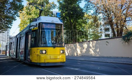 Public transportation concept. Tram yellow, modern, electric travels at Berlin's town, Germany. City and nature background.