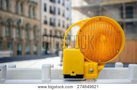 Road construction concept. Orange reflector warning light protects the drivers. Blur city background, space.