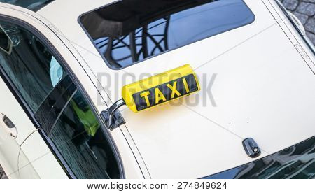 Top view from a white taxi. Yellow taxi sign and reflection of the street on window's glass. View from above, part of the car, space.