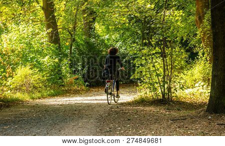 Healthy lifestyle. Woman is riding a bike in a path of Tiergarten park, between green trees, Berlin, Germany. Nature background.