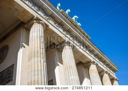 Brandenburg Gate In Berlin. Famous destination in Germany. Clear blue sky background, under view.