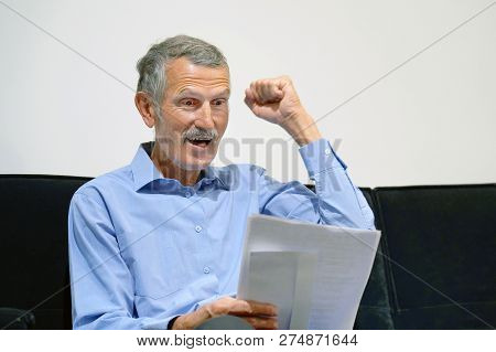 Elderly Man Enjoying Good News In Writing. The Male Reads A Letter With Good News Sitting On The Cou