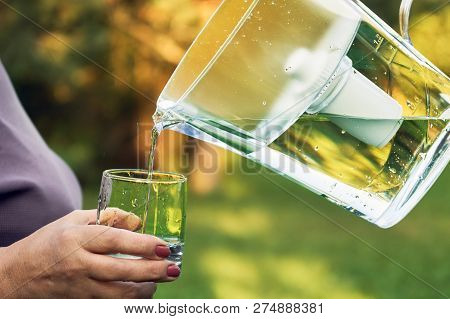 Pouring Filtered Water From A Water Filtration Jug Into A Glass Which Female Hand Holding In Summer
