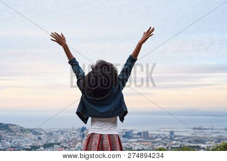 Backview of woman with arms raised, excited winning carefree
