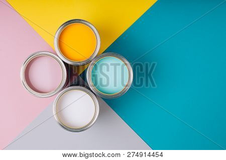 Four Open Cans Of Paint On Bright Symmetry Background. Yellow, White, Pink, Turquoise Colors Of Pain