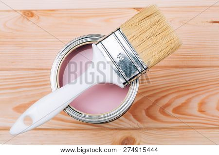 Brush With White Handle On Open Can Of Pink Color Of Paint On Natural Wooden Board. Renovation Conce