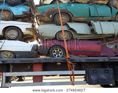 Three Colorful Discarded Scrap Cars Stacked On A Junkyard, Concept For Insurance Or Waste Management
