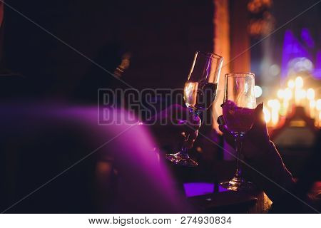 Christmas Illuminations And Champagne Glasses. Hands Of People With Glasses Of Champagne, Celebratin