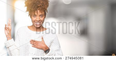 Beautiful young african american woman wearing winter sweater over isolated background Swearing with hand on chest and fingers, making a loyalty promise oath