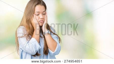 Young beautiful brunette business woman over isolated background Tired hands covering face, depression and sadness, upset and irritated for problem