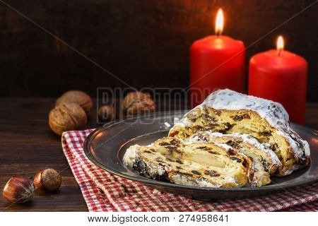 Christmas Cake, German Christstollen With Fruits, Raisins And Marzipan In Front Of Two Red Candles A