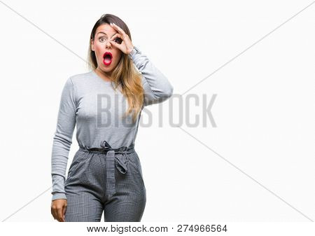 Young beautiful worker business woman over isolated background doing ok gesture shocked with surprised face, eye looking through fingers. Unbelieving expression.