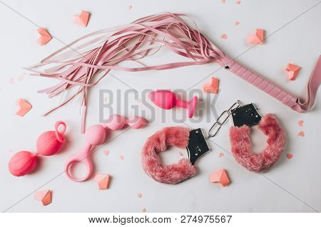 Various Pink Sex Toys Are Arranged On A White Background With Pink Hearts. Romantic Background For G