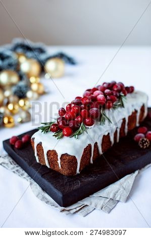 Traditional Christmas Fruitcake With Holly Berry Decoration On Black Wooden Board And White Backgrou