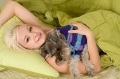Caucasian woman lying down on bed and holding dog of Schnauzer breed poster