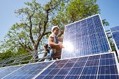 Young technician sitting on metal platform adjusting heavy solar photo voltaic panel on blue sky and green tree background. Stand-alone solar panel system installation and professionalism concept. poster