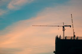 Crane And Building Construction Site At Sunset. High-quality Stock Photo Image Silhouette Of Constru