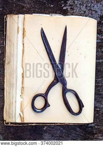 Vintage Scissors On The Old Book And Wooden Background Closeup