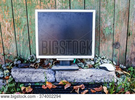 Old And Dirty Computer Monitor On The Weathered Paint Wall Background Outdoor