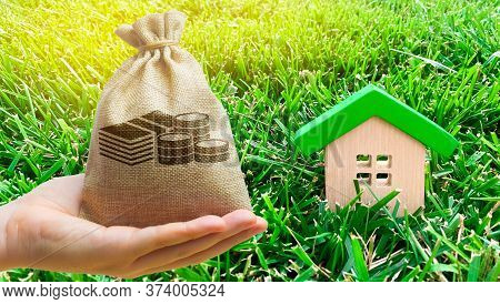 Miniature Wooden House And Money Bag On Grass. Real Estate Concept. Eco-friendly And Energy Efficien