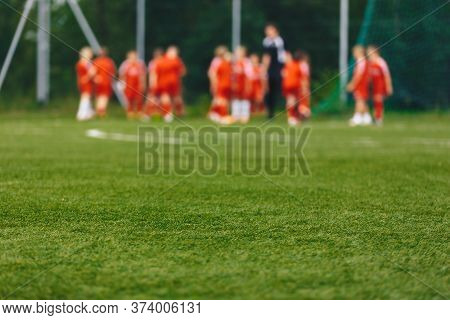 Blurred Background Of Sports Team With Coach On Training Field. Soccer Summer Training Camp. Footbal