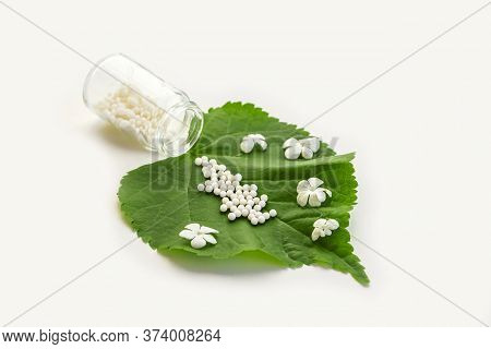 Homeopathic Globules And Glass Bottle On A Green Plant Leaf On White Background. Concept Of Healthca
