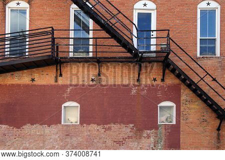 Arched White Windows Behind Back Alley Fire Escape Stairs At An Old Faded Brick Building