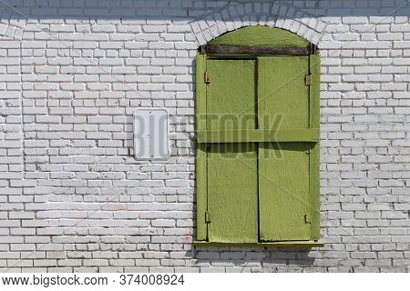 A Bright Green Shutter Window Against A Bright White Brick Wall