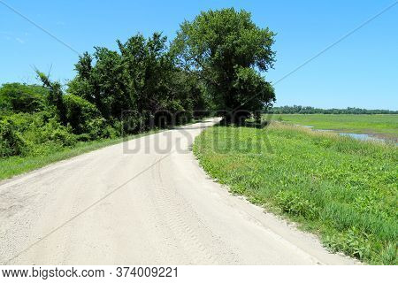 A Natural Dirt Road Leading Into Beautiful Farmland Near A Meadow Pond And Glade