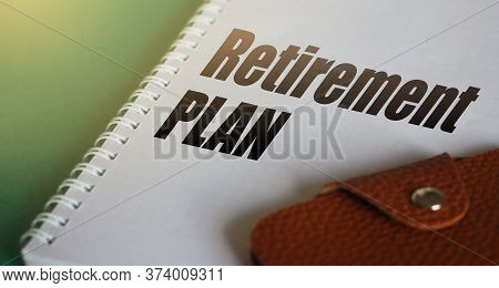 Retirement Plan Wods On A Copybook Page And Brown Leather Wallet On Table. The Concept Of Successful