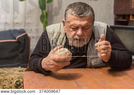 Indoor Portrait Of Senior Ukrainian Peasant Taking Clew Of Thread While Sitting At Old Table