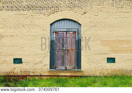 A Painted Yellow Brick Building With Boarded Up Green Entrance Door And Grass Front With Rusty Pipes