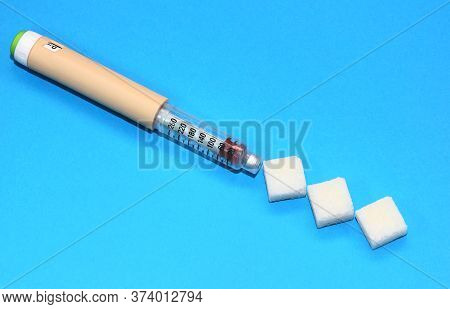 Insulin Syringe Pen On Blue Background With Lump Sugar. Insulin Administration And Glucose Regulatio