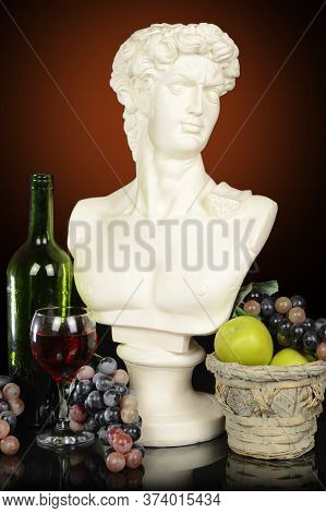 A Roman Head Bust Of A Man Surrounded By Fruits And Wine With A Gradient Background.