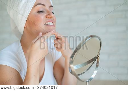 A Woman Looks In A Table Mirror And Crushes Acne On Her Chin. An Unhappy Girl With Problem Skin Does