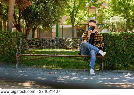 Guy With A Mask Is Sitting On A Bench While He Speaks With His Mobile. Lifestyle, Coronavirus