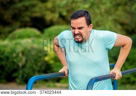 Trying To Get Back Into Shape: Middle-aged Man With Extremely Stressed Face Doing Dips On Parallel B