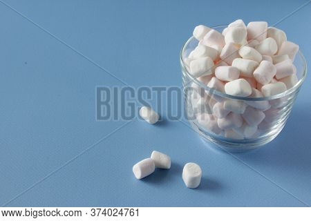 White Fluffy Marshmallows In White Cup Isolated On Blue Background. Mini Marshmallows. Winter Food B