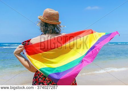 Woman In Hat With Lgbt Flag At The Beach. Girl Holds An Rainbow Flag While Standing On The Beach, Ba